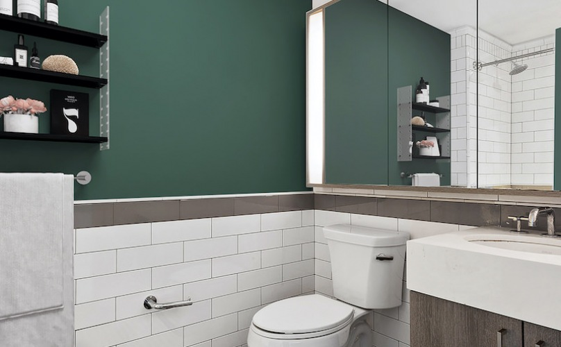 Bathroom with white tile lower walls and large mirror with side lights